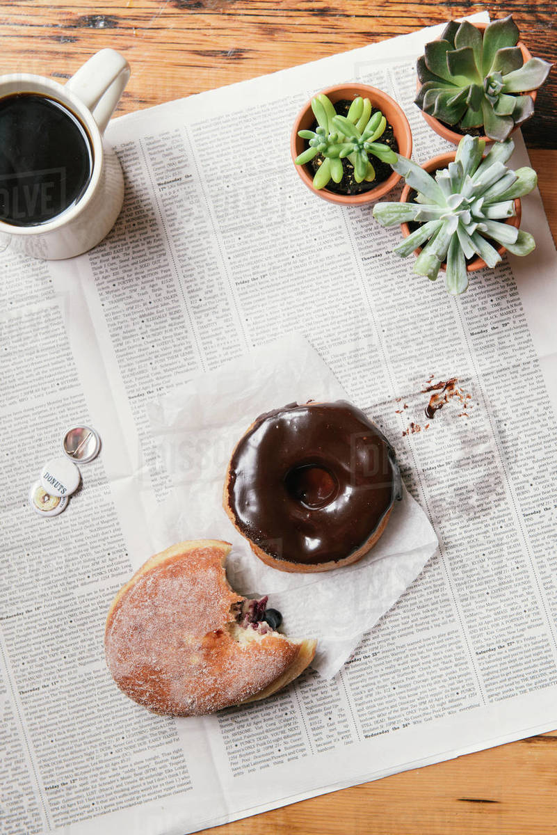 Messy chocolate and jelly donuts with coffee and morning newspaper Royalty-free stock photo