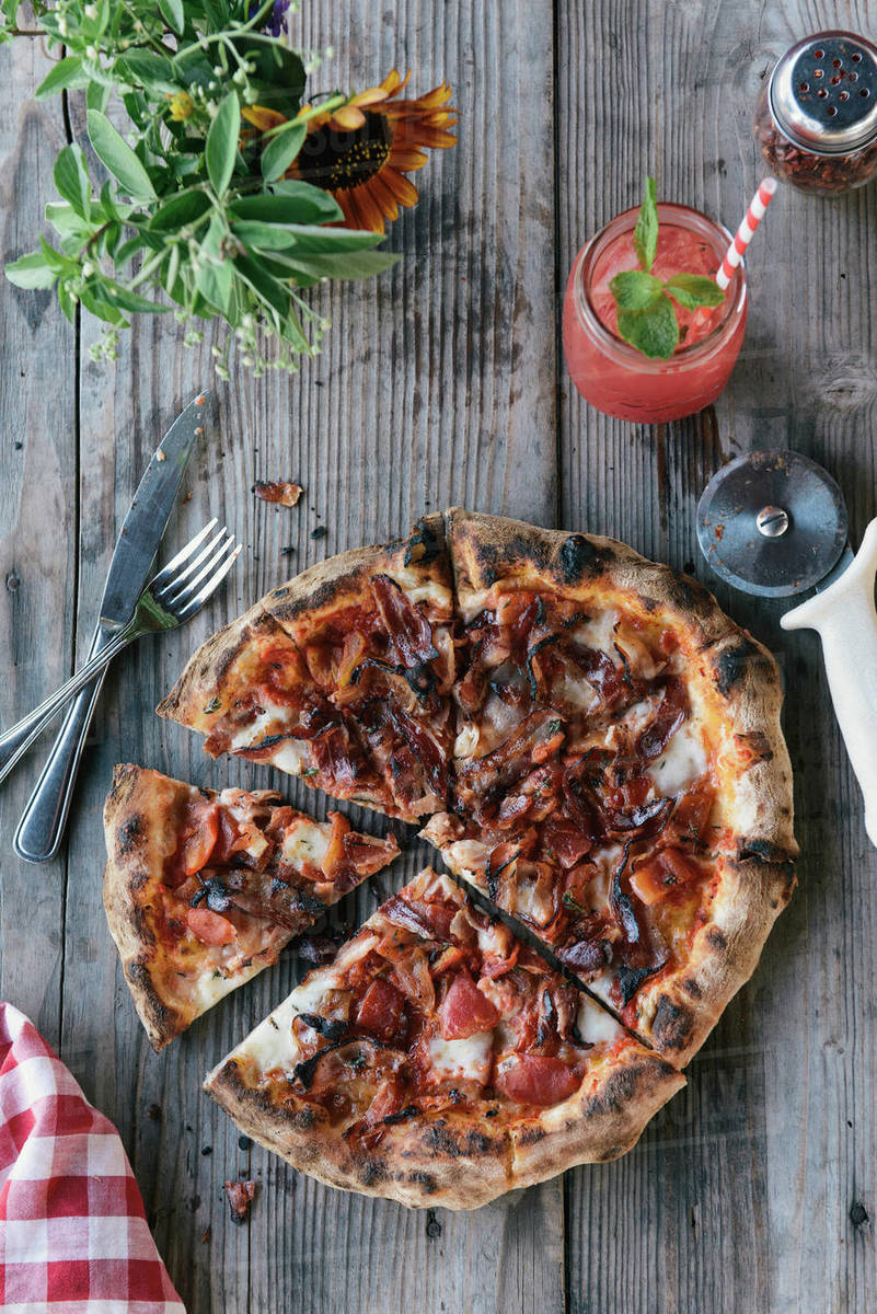 Sliced pizza served from the oven on picnic table outdoors on farm Royalty-free stock photo