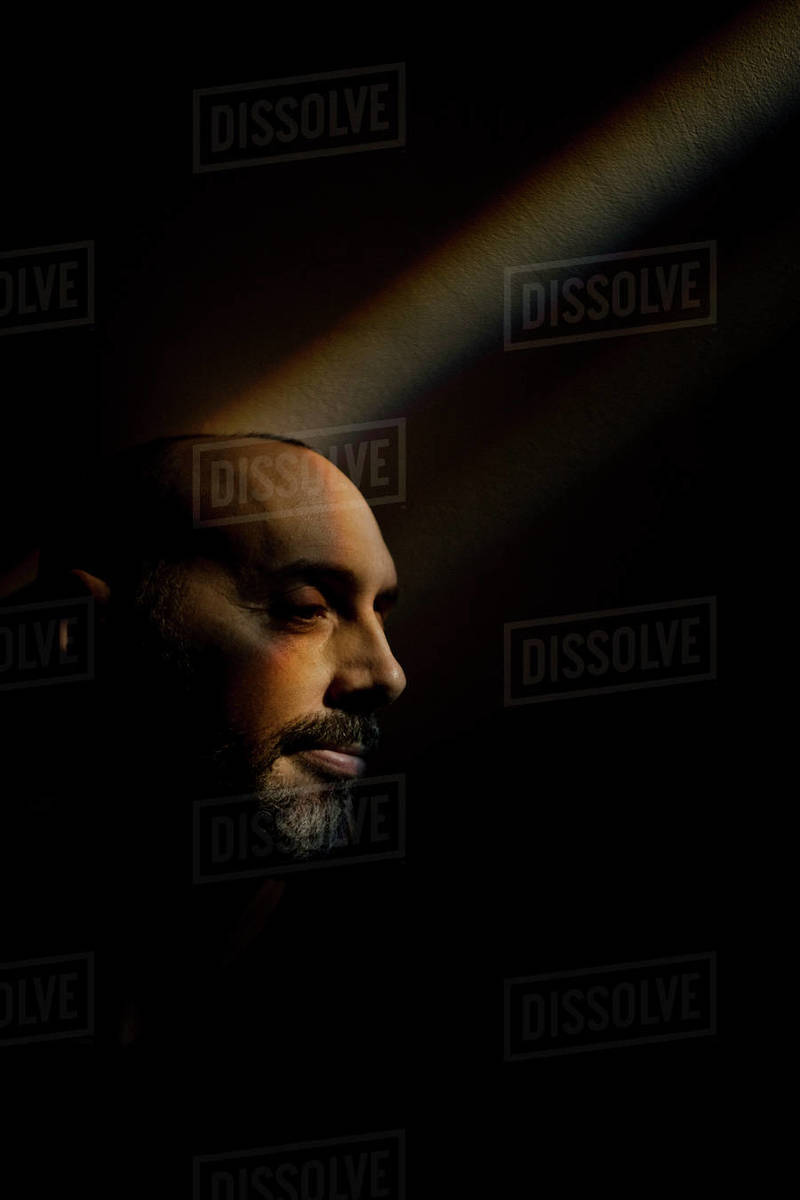 Man sitting in a rainbow beam along a dark wall in basement Royalty-free stock photo