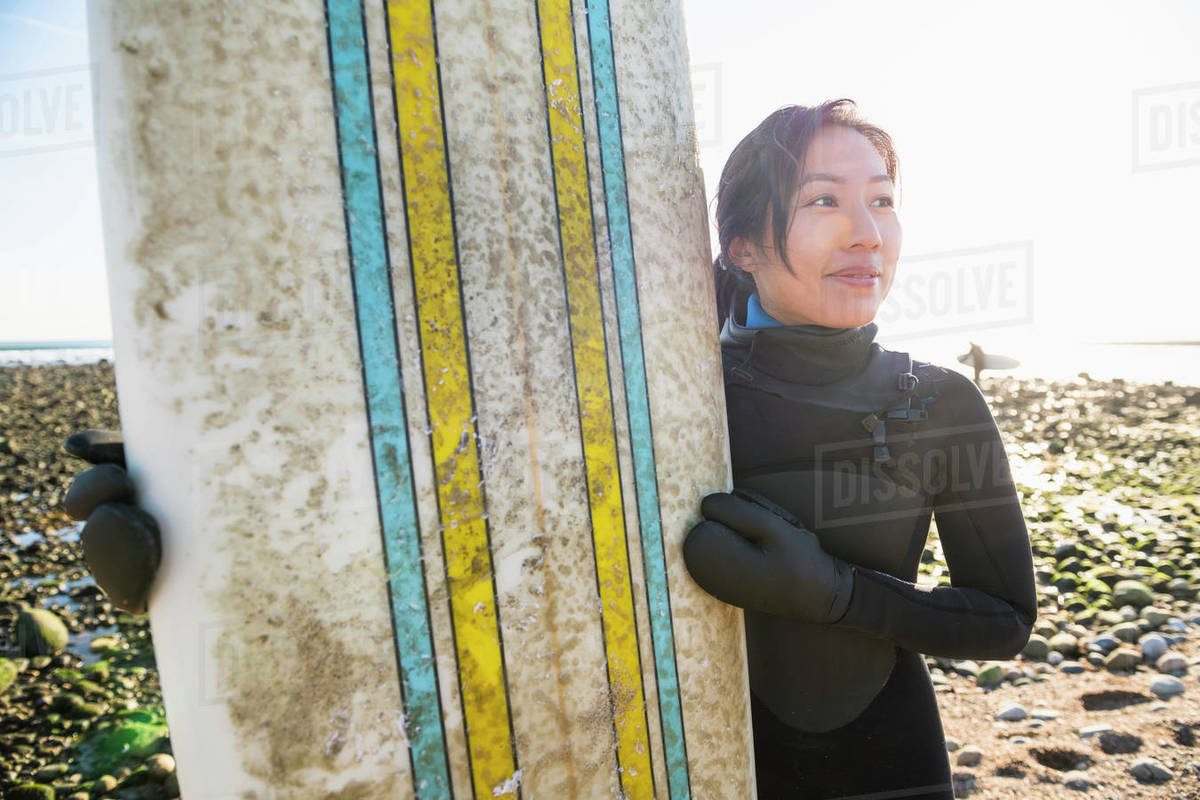 Smiling Asian Woman with a healthy lifestyle going winter surfing Royalty-free stock photo