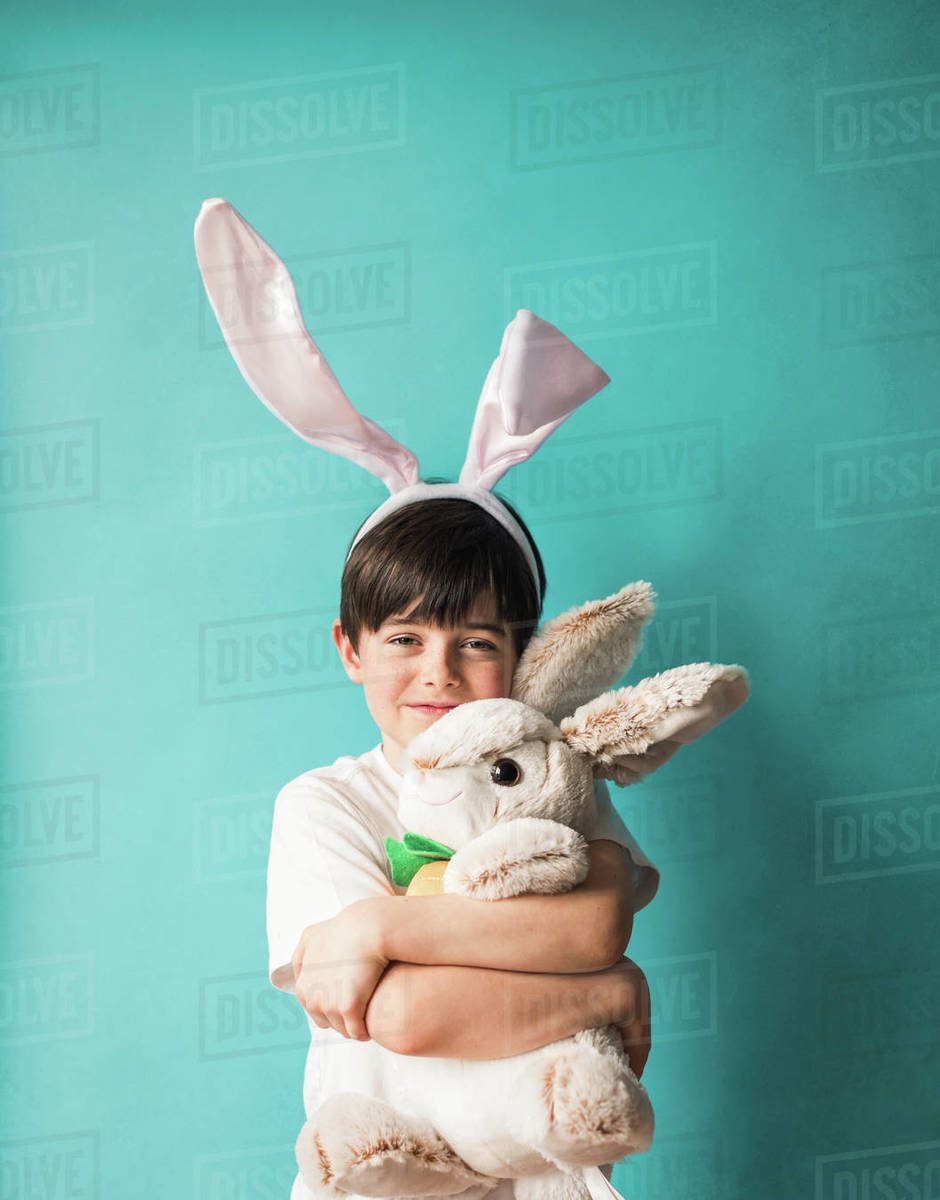 Boy wearing bunny ears hugging toy rabbit against blue background. Royalty-free stock photo