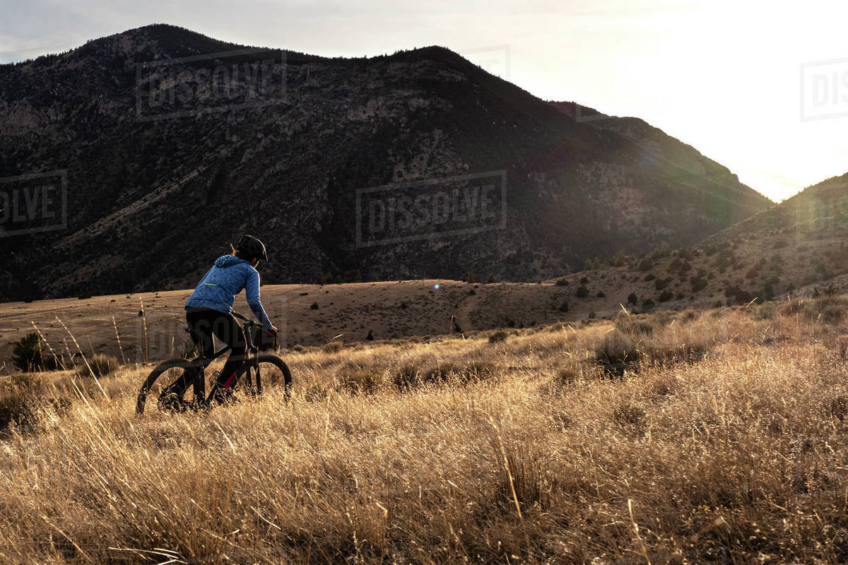 Young woman mountain biking uphill during sunset in mountains Royalty-free stock photo