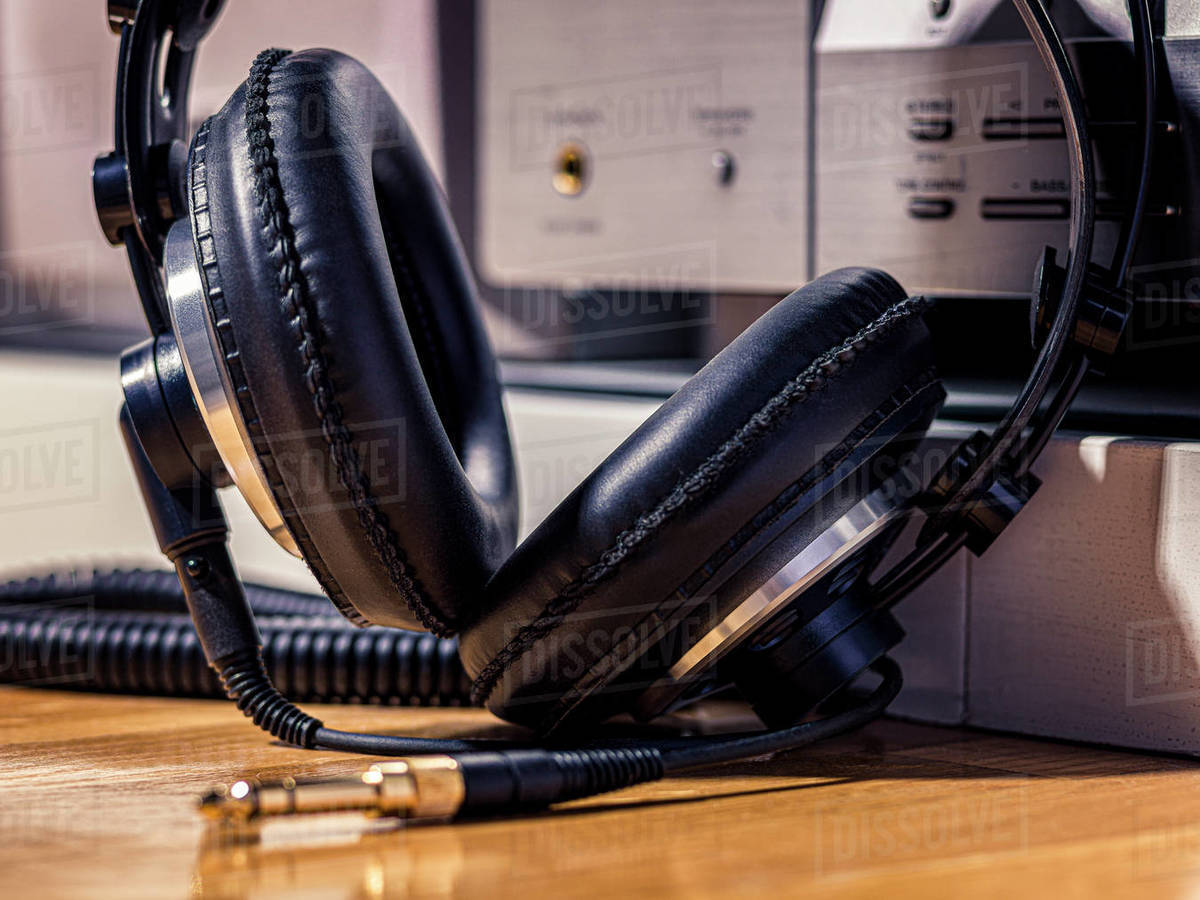 Black Hi-Fi headphones with a gold input jack on a wooden floor Royalty-free stock photo