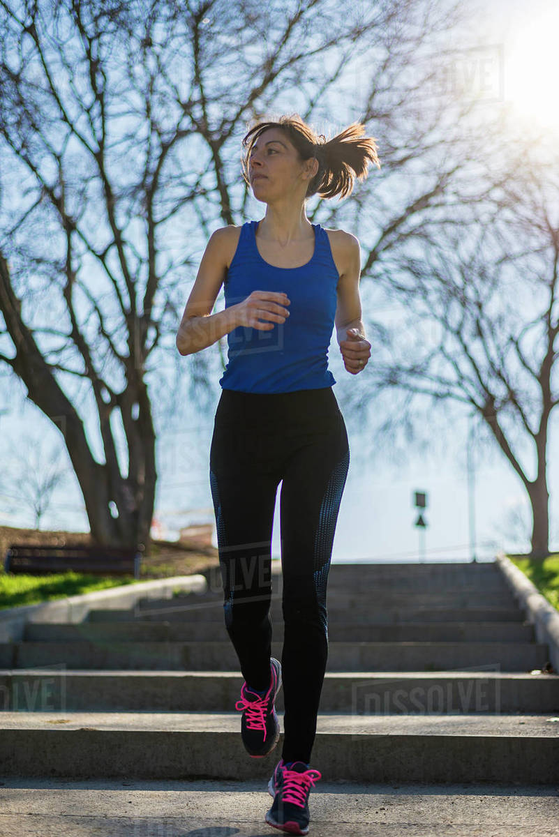 Portrait of a woman running on staircase outdoors in a park Royalty-free stock photo