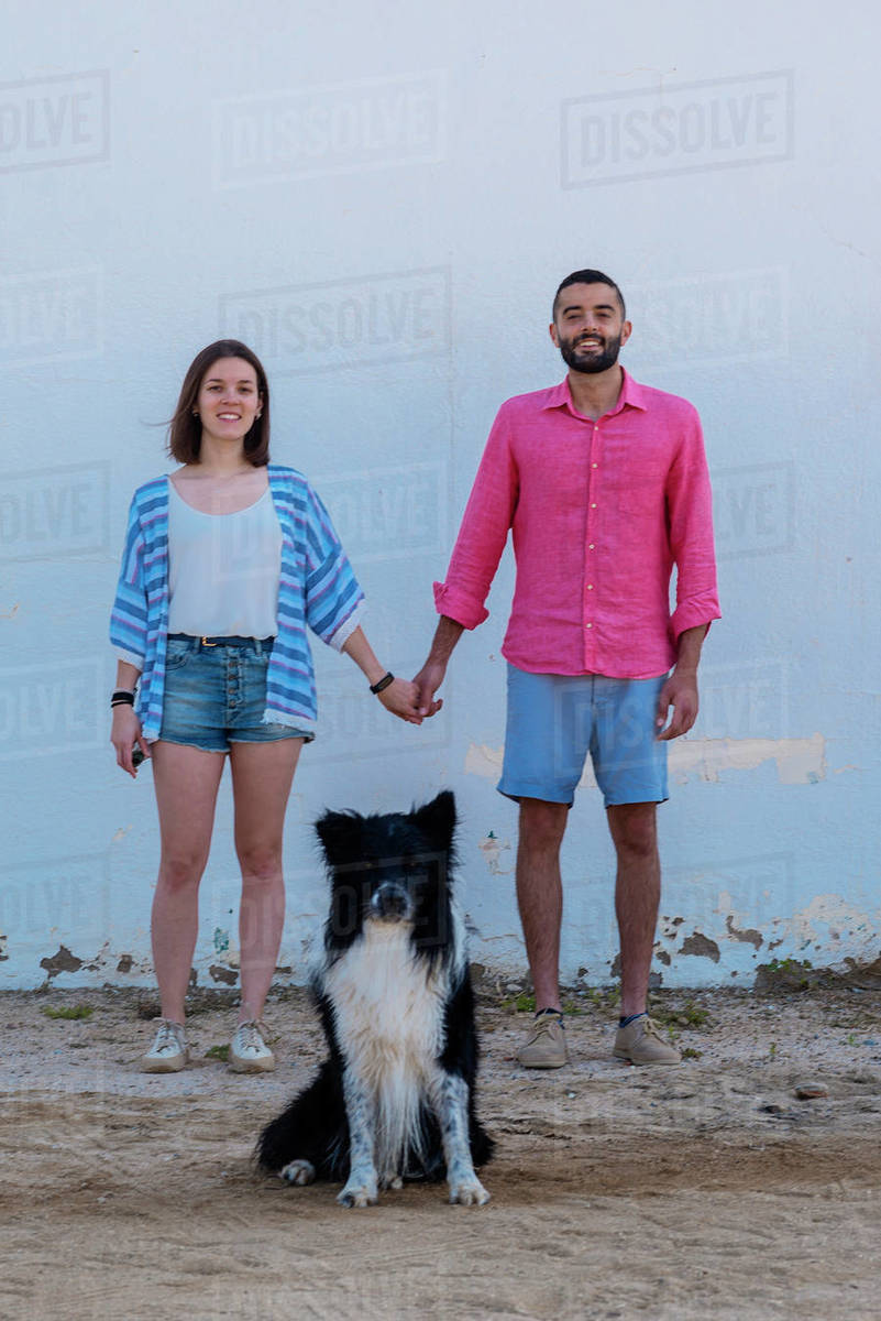 Happy couple standing with dog against wall while holding hands Royalty-free stock photo