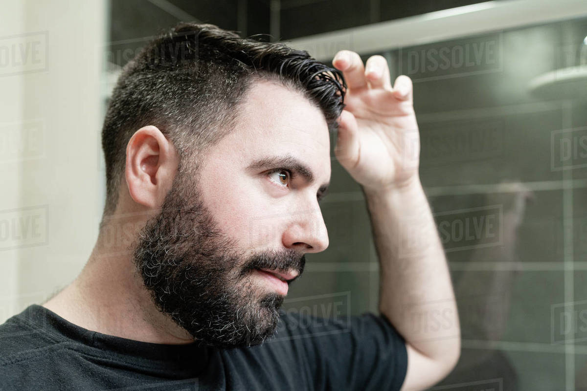 Self haircut. A man is combing his hair in the bathroom Royalty-free stock photo