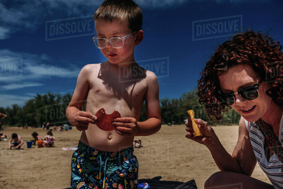 Young boy eating meat and cheese on the beach Royalty-free stock photo