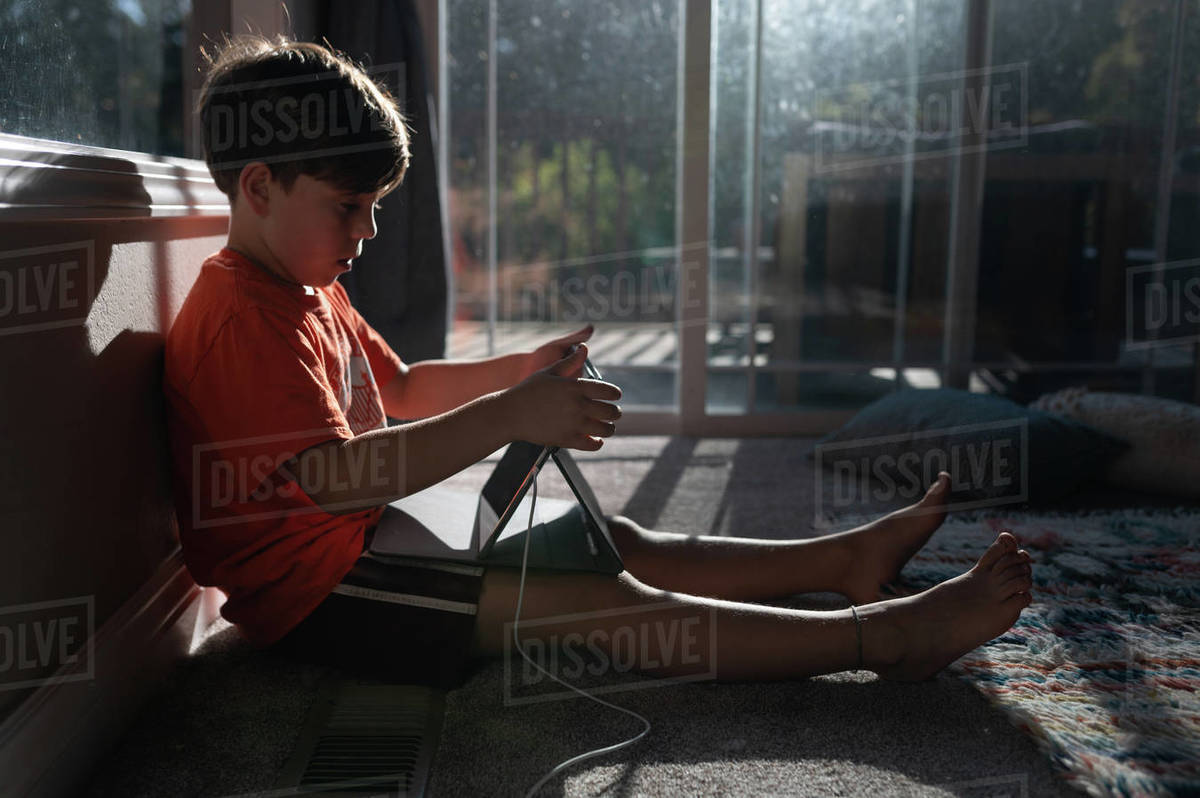 Boy using ipad tablet on the floor of his home with sun in window Royalty-free stock photo