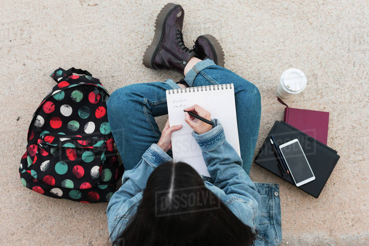 Top view of a college student while she writes in her notebook Royalty-free stock photo