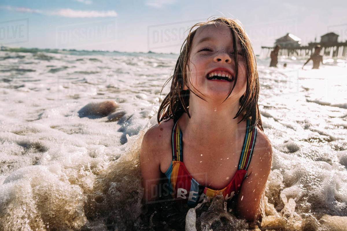 Young girl playing laying on beach while a wave crashes on her Royalty-free stock photo