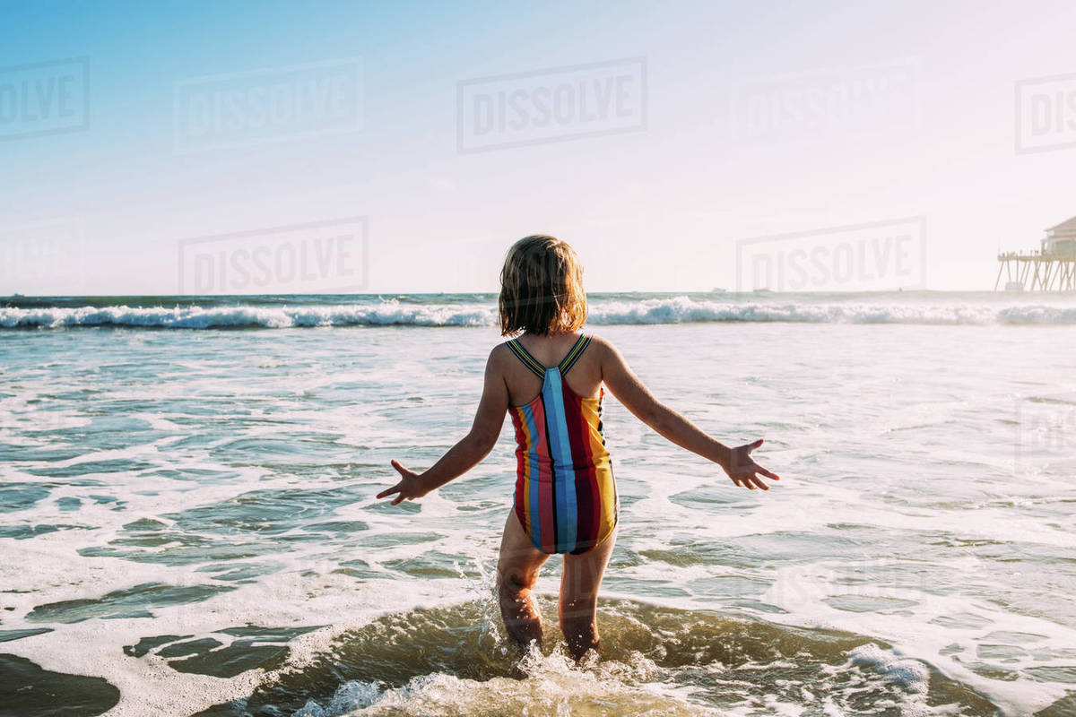 Behind shot of young girl running into ocean Royalty-free stock photo