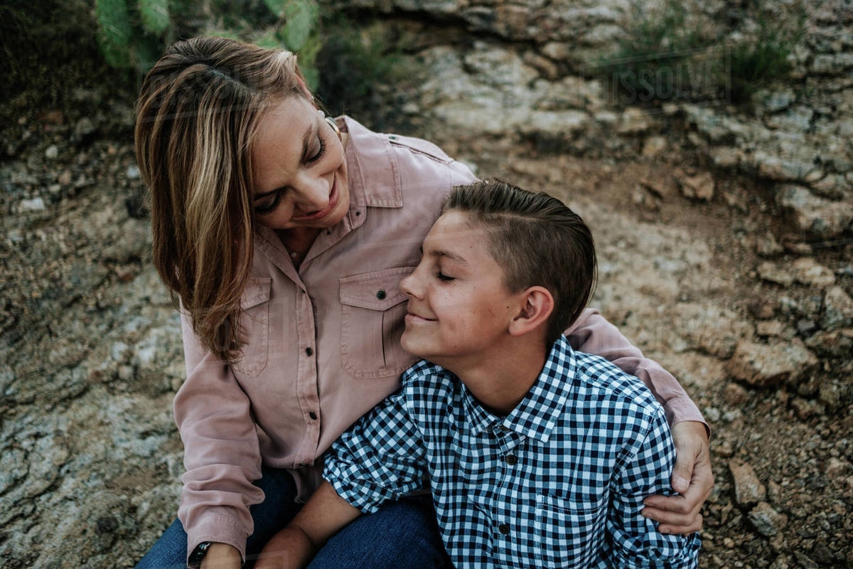 Mother hugging non binary child while sitting on rocks Royalty-free stock photo