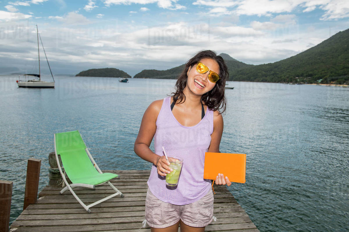Woman holding drink on pier at the tropical island of Ilha Grande Royalty-free stock photo