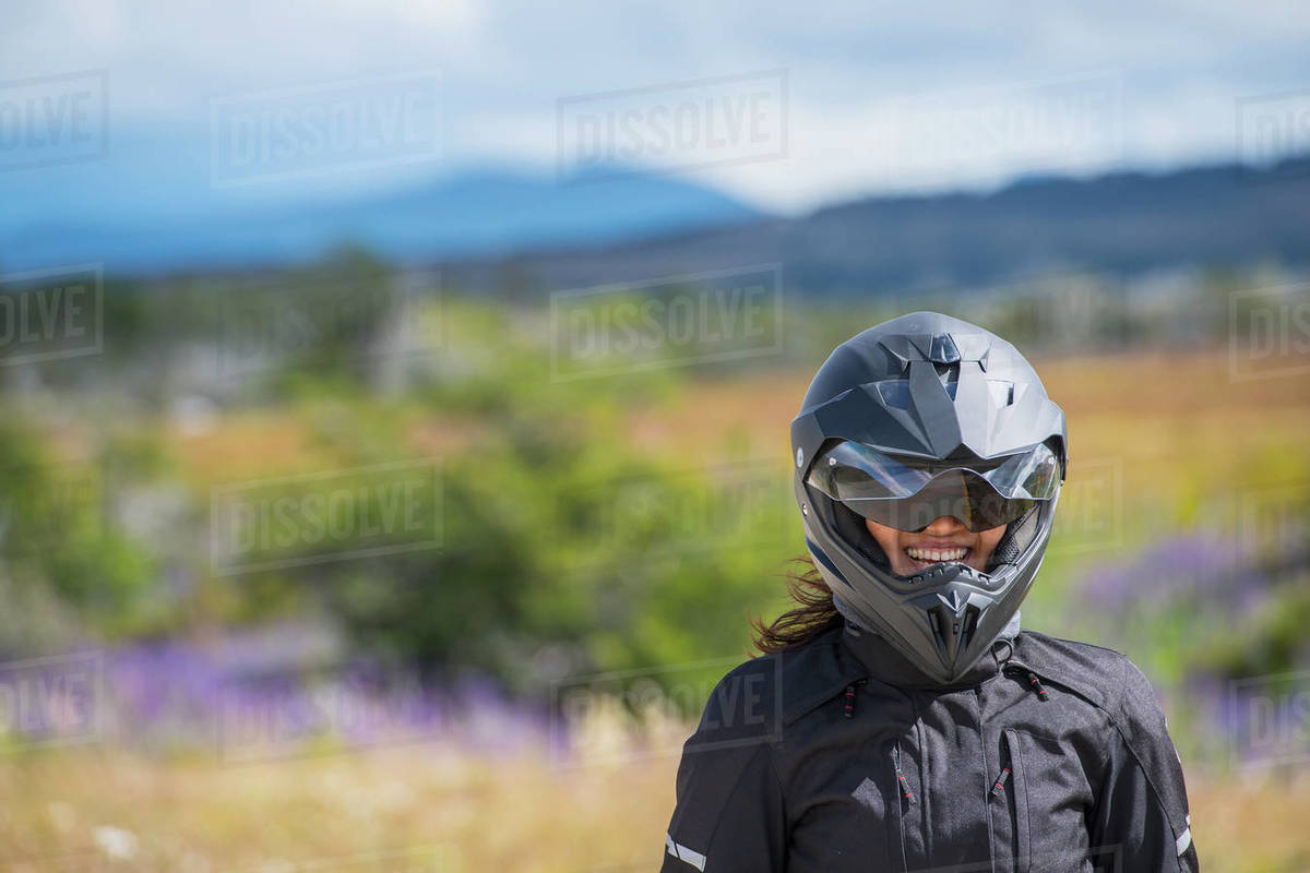Woman in motorbike clothes and helmet laughing at camera, Puerto Natal Royalty-free stock photo