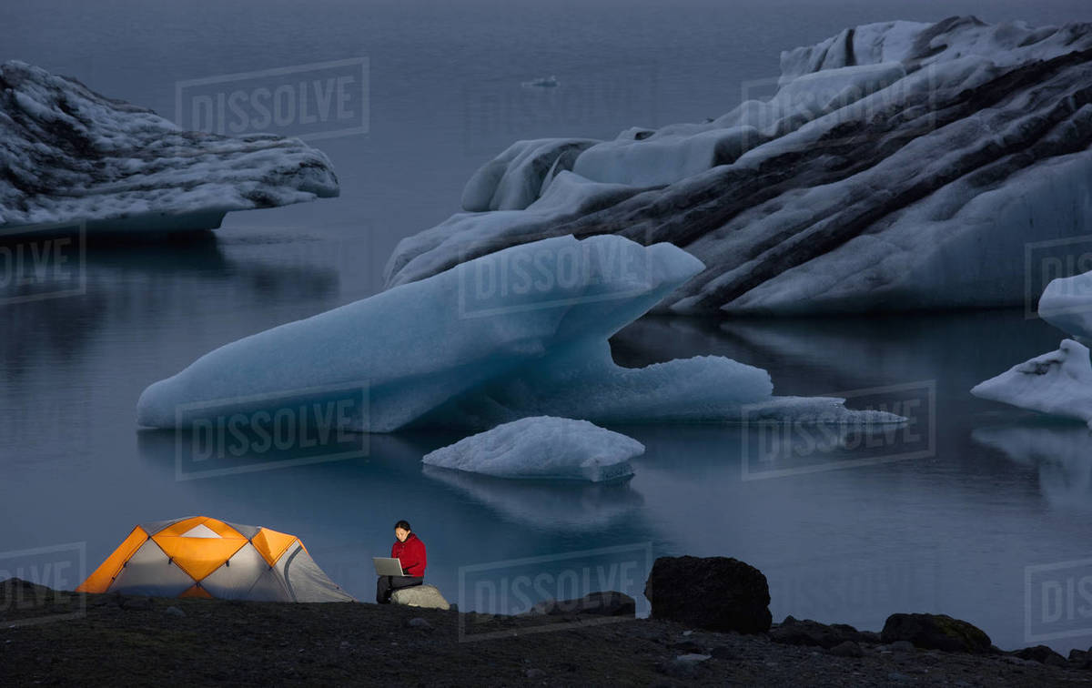 Woman using her laptop at campsite by glacier lagoon Royalty-free stock photo