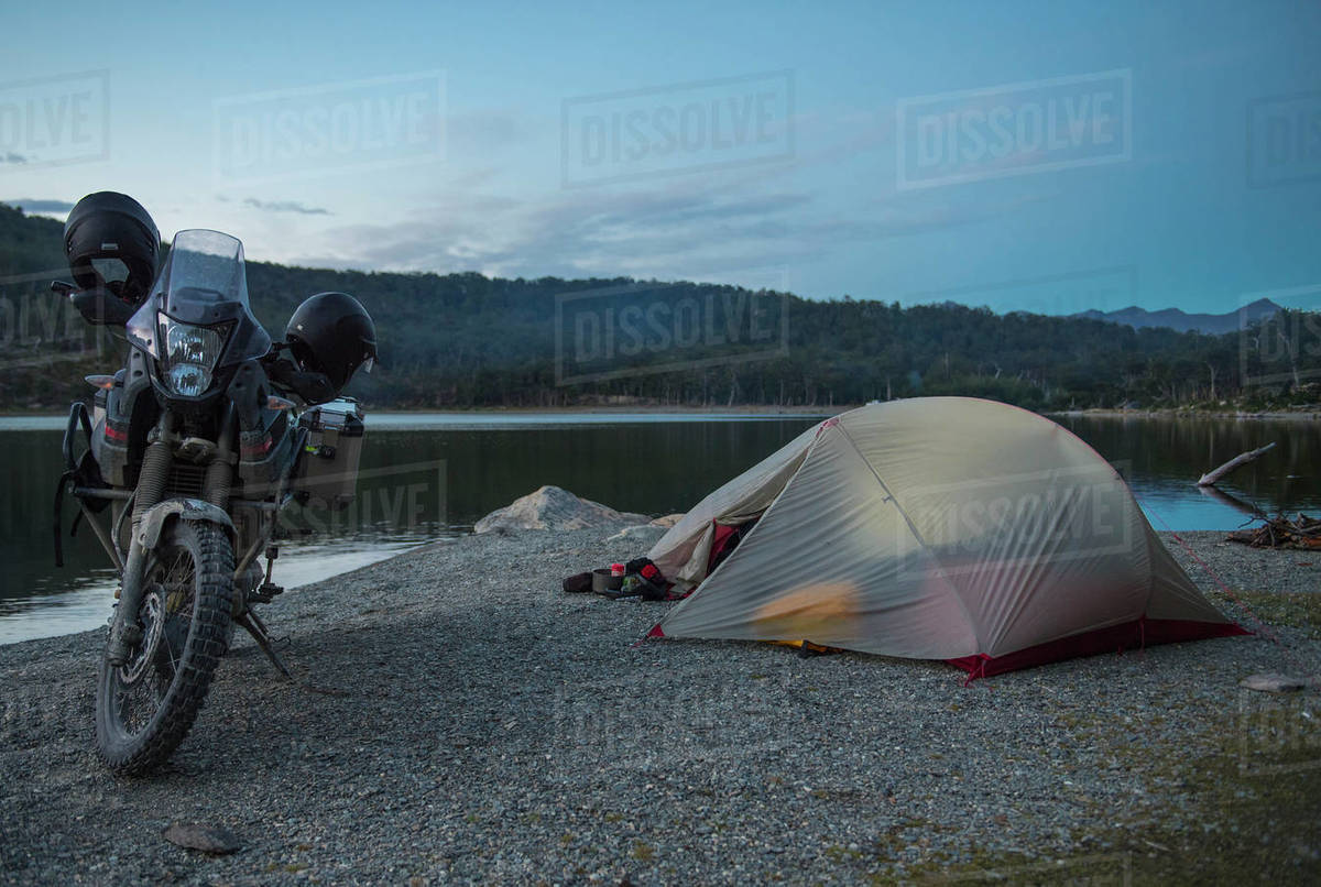 Camp with touring motorbike next to still lake on Tierra del Fuego Royalty-free stock photo