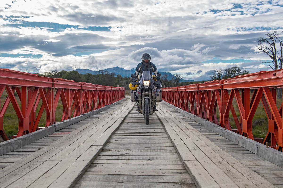Man on off road touring motorbike crossing wooden bridge Royalty-free stock photo