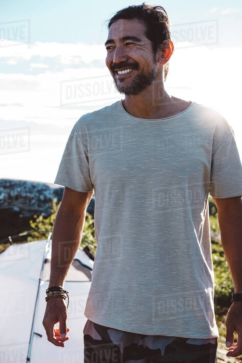 Smily man lit by the sun in a camp site Royalty-free stock photo