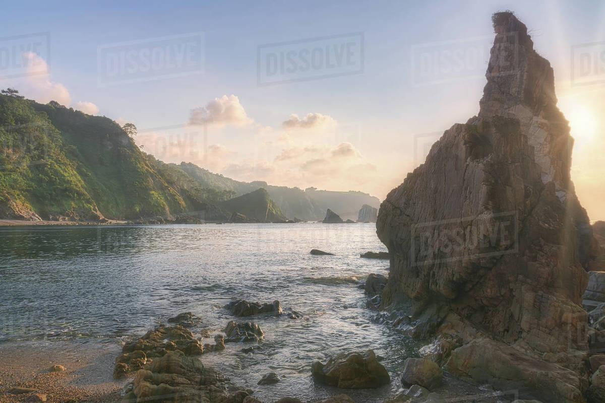 Nice sunset over the ocean behind a rock formation Royalty-free stock photo