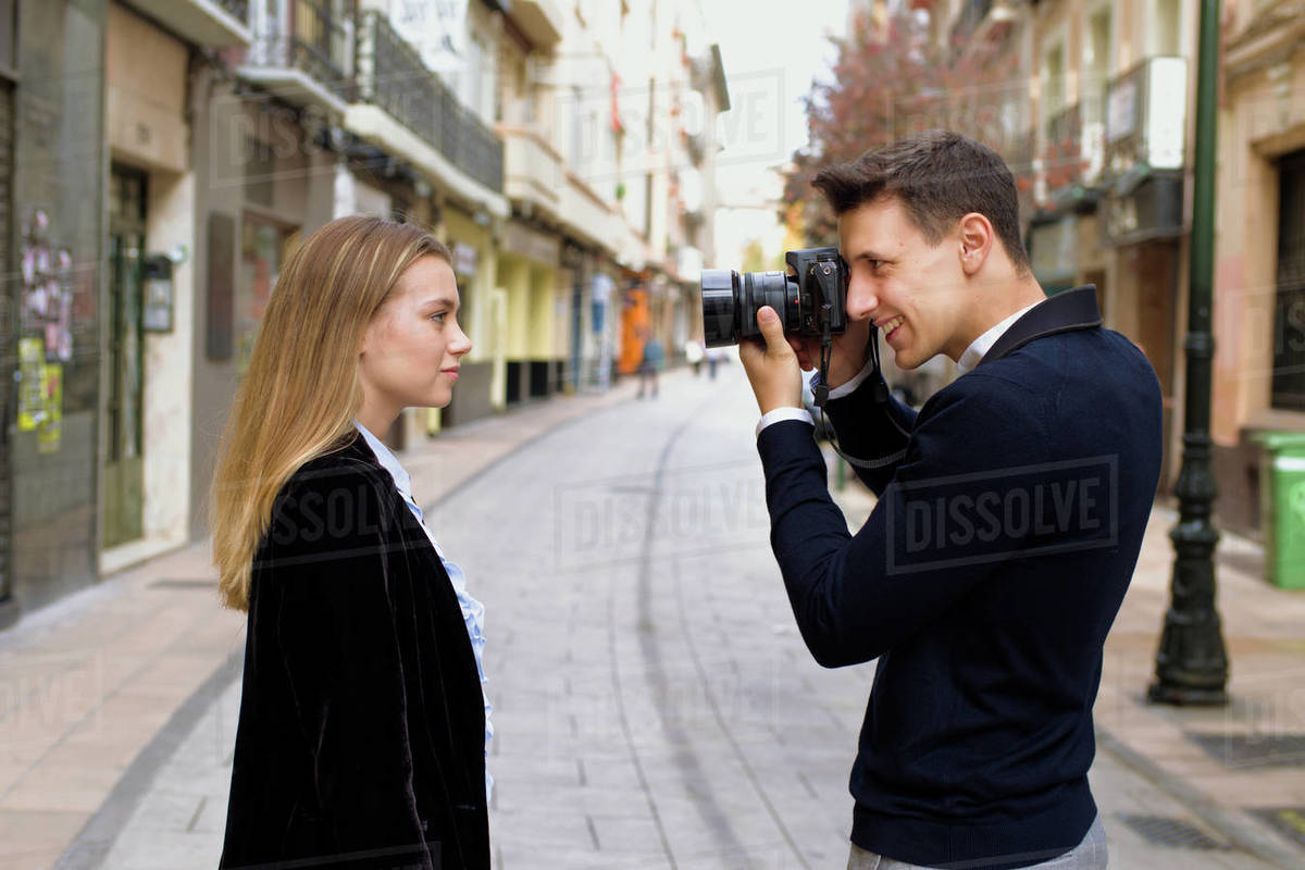 Young man photographs his friend on the street of a European city Royalty-free stock photo
