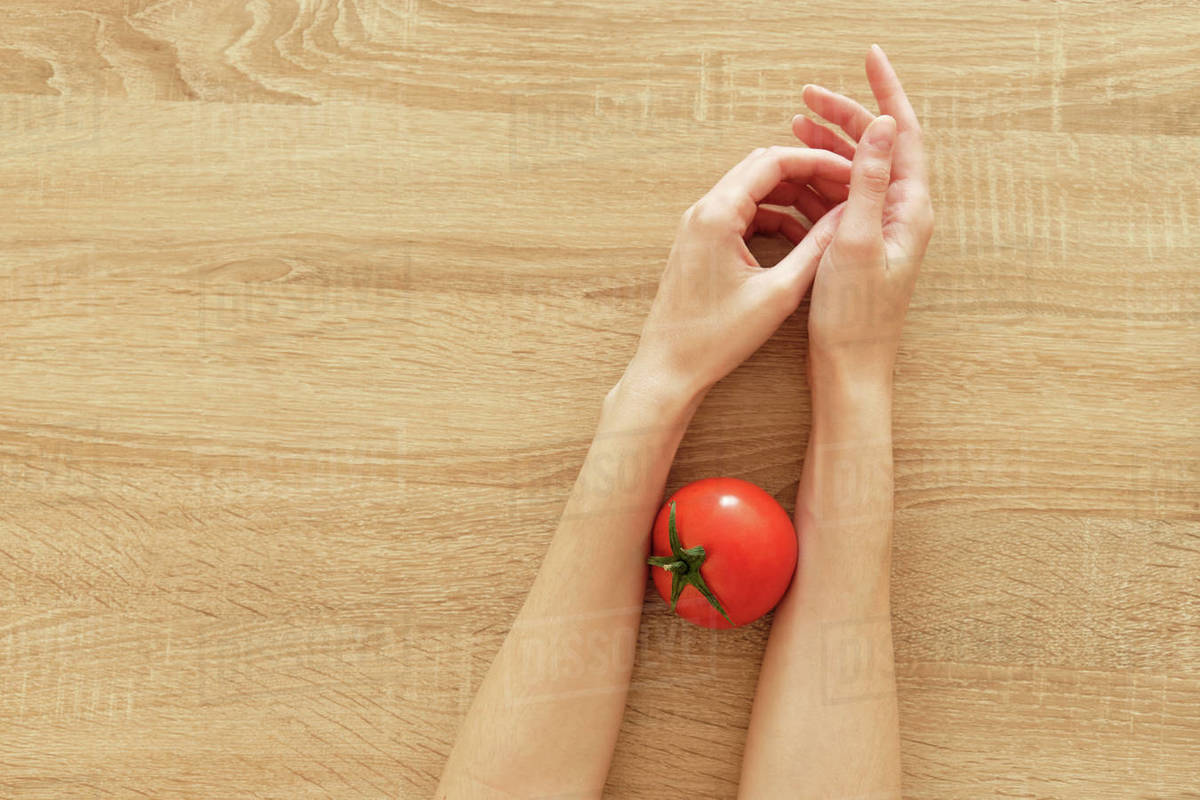 Juicy tomato in hands on wooden background tomato-ˈmätō,təˈmātō Перекл Royalty-free stock photo