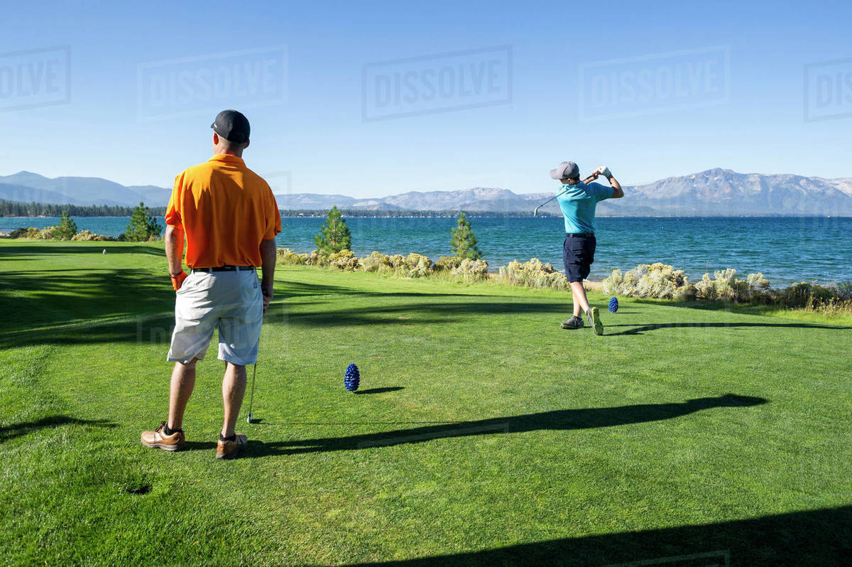 Two men playing golf at Edgewood Tahoe in Stateline, Nevada. Royalty-free stock photo