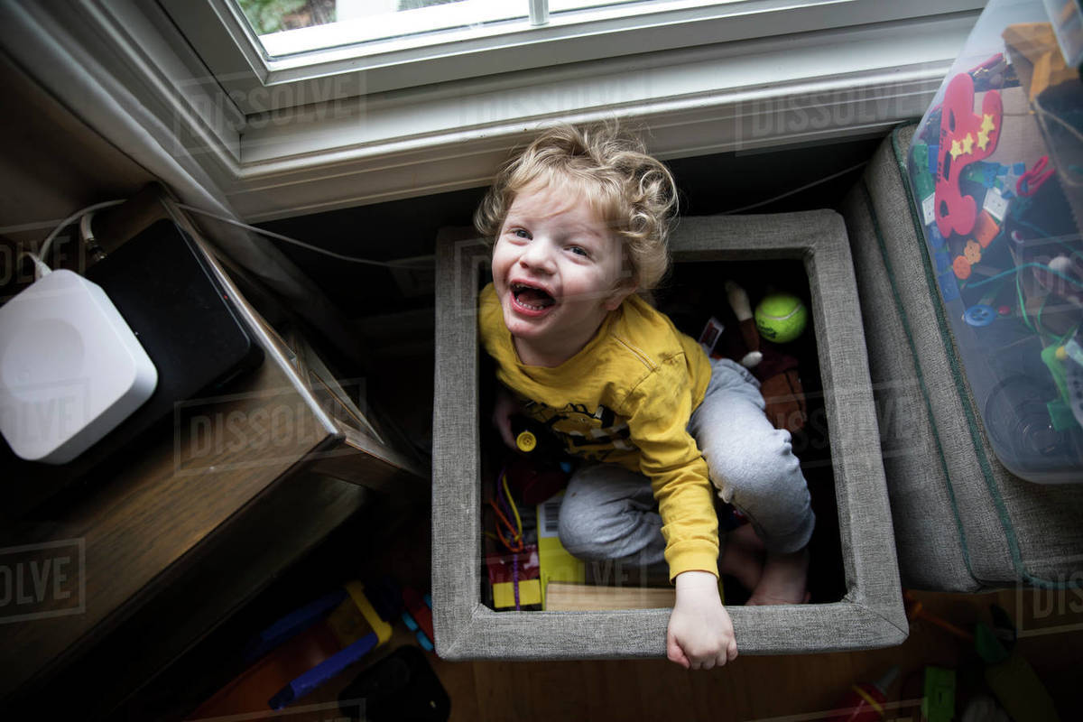 Laughing Boy Sits in Toy Box Next to Storage Bins Looks Up at Camera Royalty-free stock photo