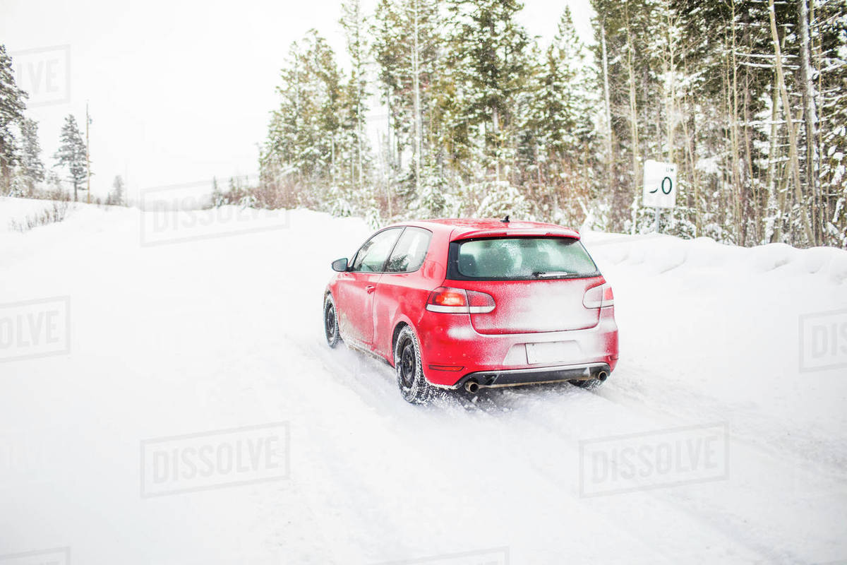 Rear view of red car driving on a snowy road. Royalty-free stock photo