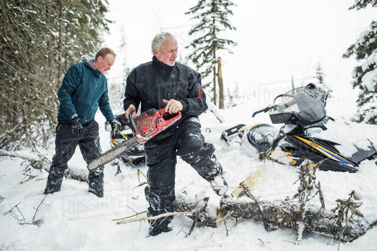 Retired man and son using chainsaw to clear trails while snowmobiling. Royalty-free stock photo