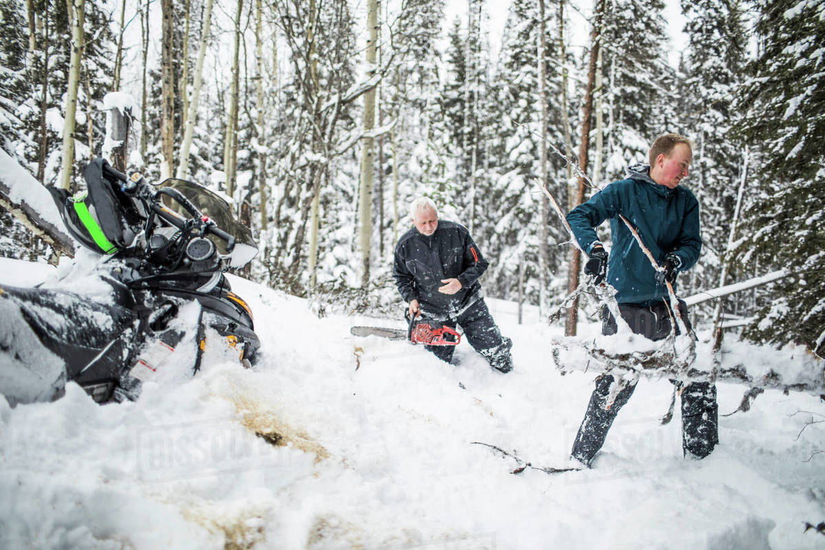 Father and son clearing trails while snowmobiling. Royalty-free stock photo
