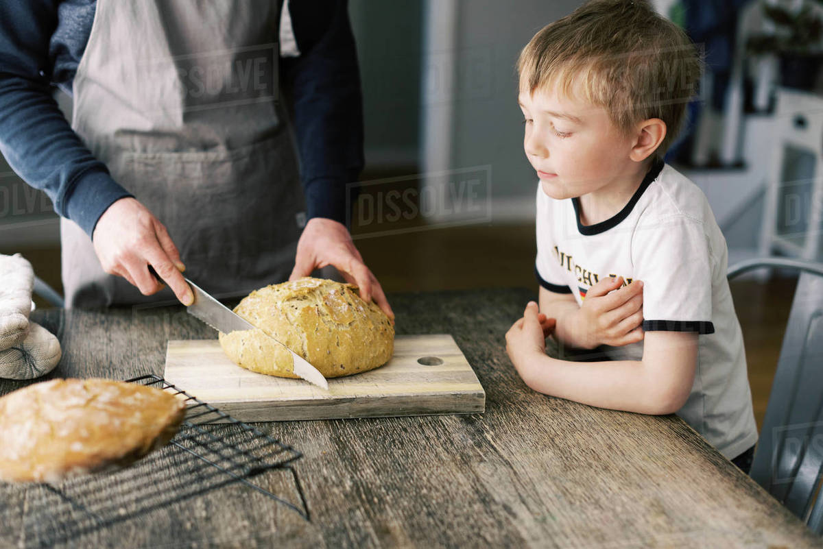 Man cutting a fresh loaf of bread for lunch. Royalty-free stock photo