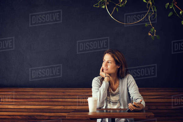 Thoughtful woman looking away while sitting at cafe table Royalty-free stock photo