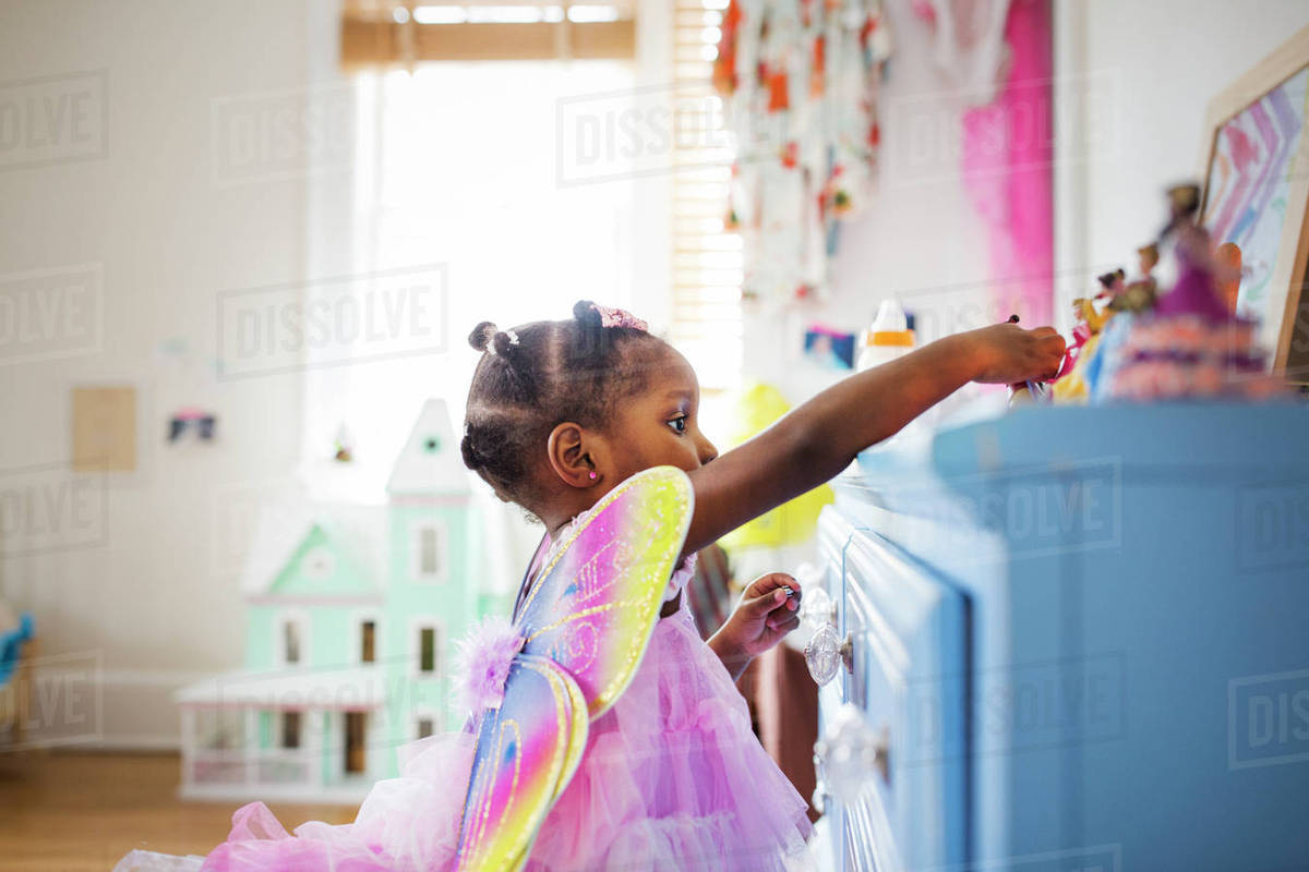 Side view of girl dressed in fairy costume playing with toys at home Royalty-free stock photo