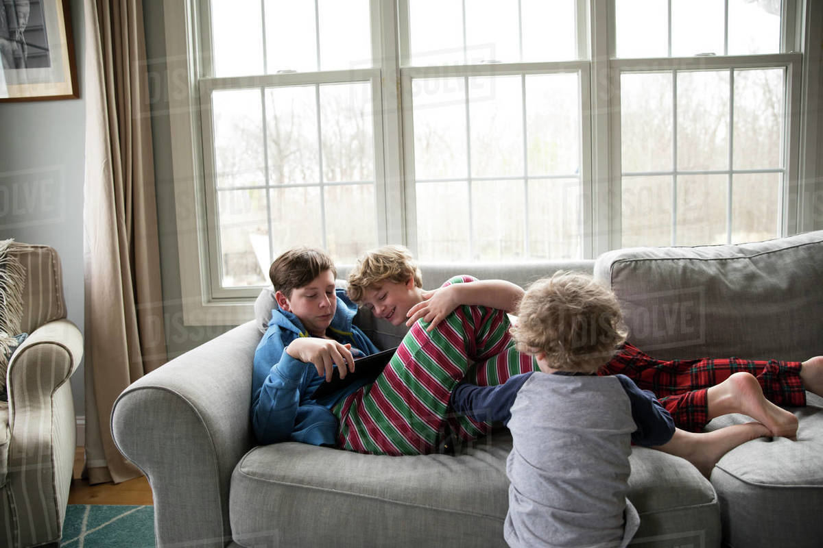 Teen Brother With Flu Plays Ipad, Little Brothers Watch Royalty-free stock photo