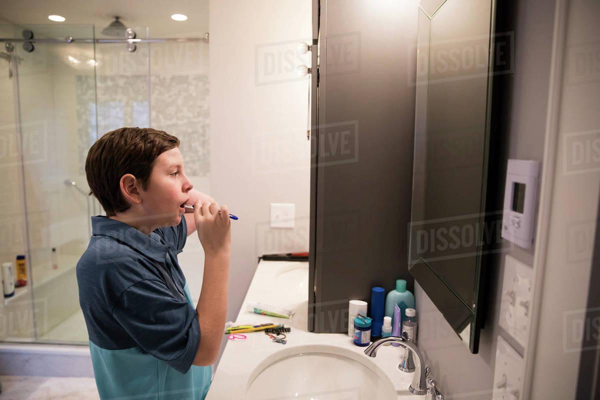 Teen Boy Looks in Mirror While Brushing His Teeth in Modern Bathroom Royalty-free stock photo