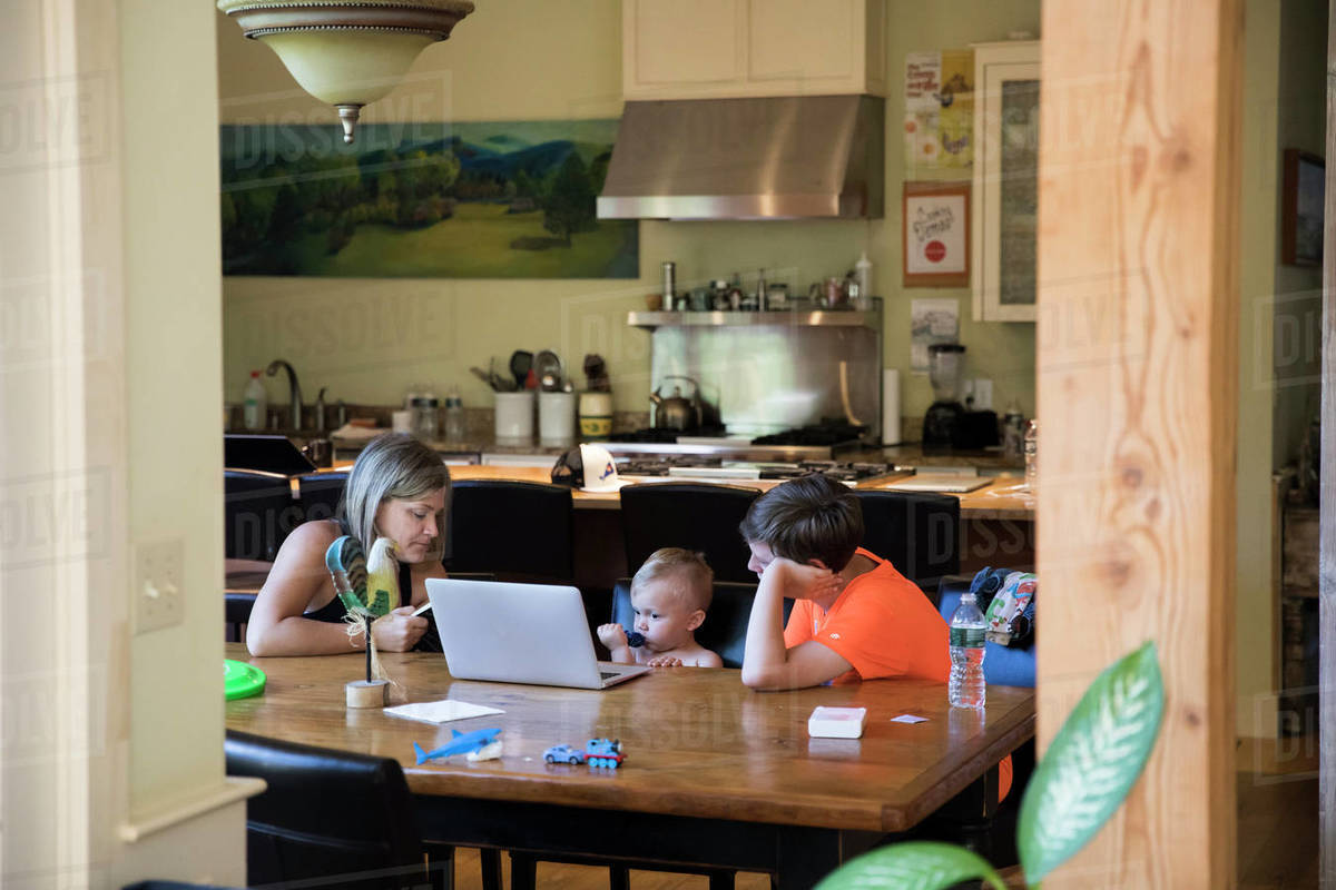 Wide View of Mom at Table With Toddler Son on Laptop and Teen Cousin Royalty-free stock photo