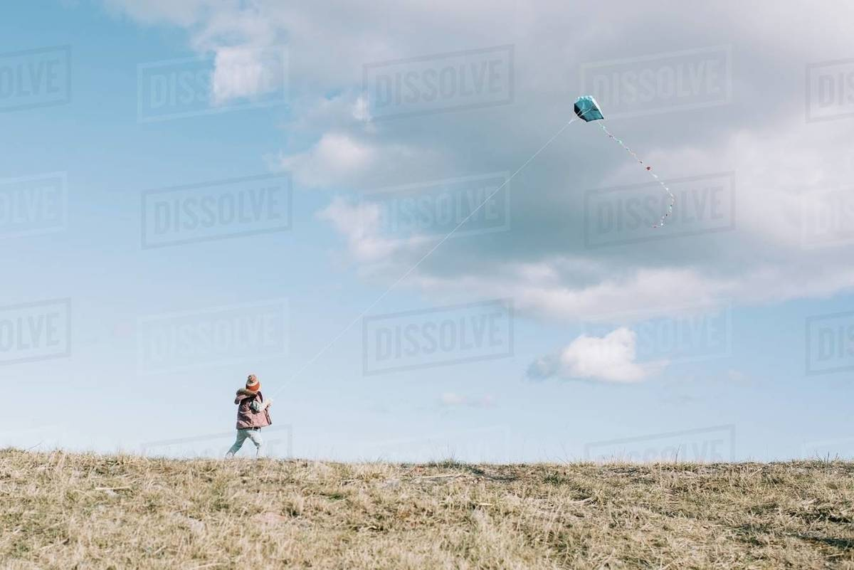 Girl flying a kite at the top of a hill with a fluffy cloud sky Royalty-free stock photo