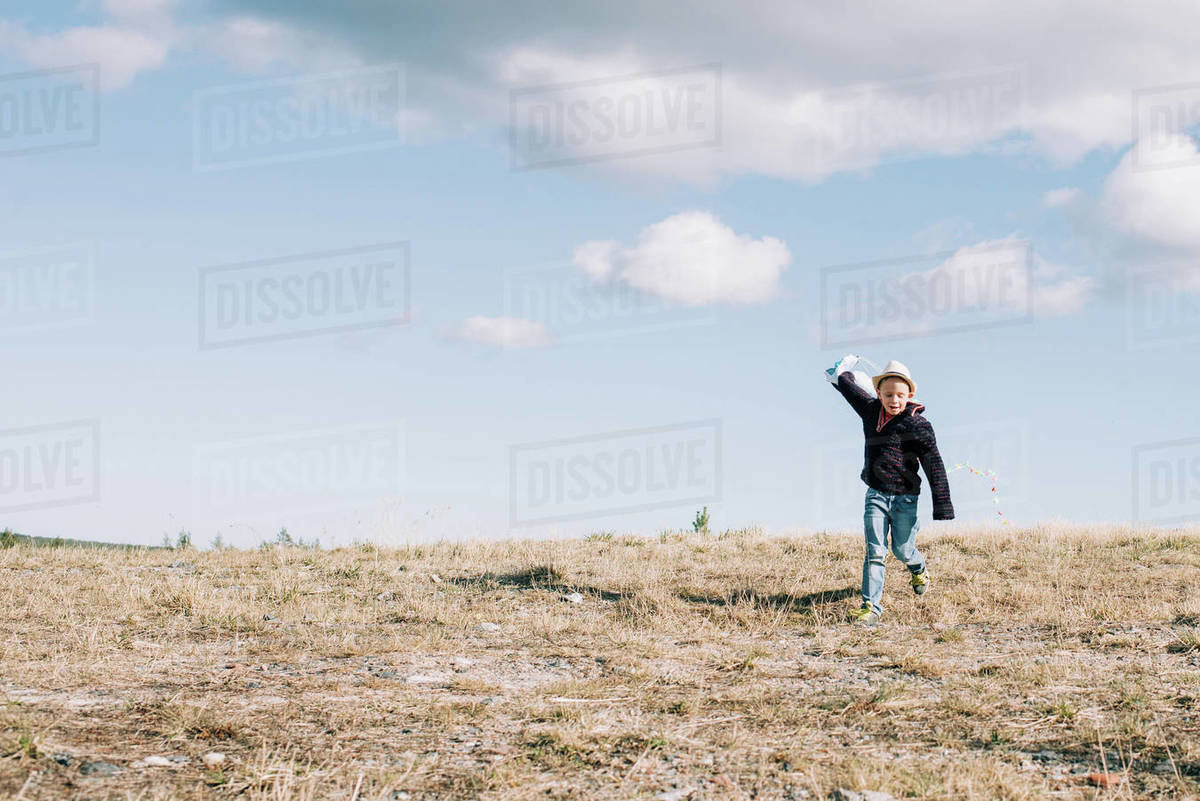 Young boy running with a kite at the top of a hill on a sunny day Royalty-free stock photo
