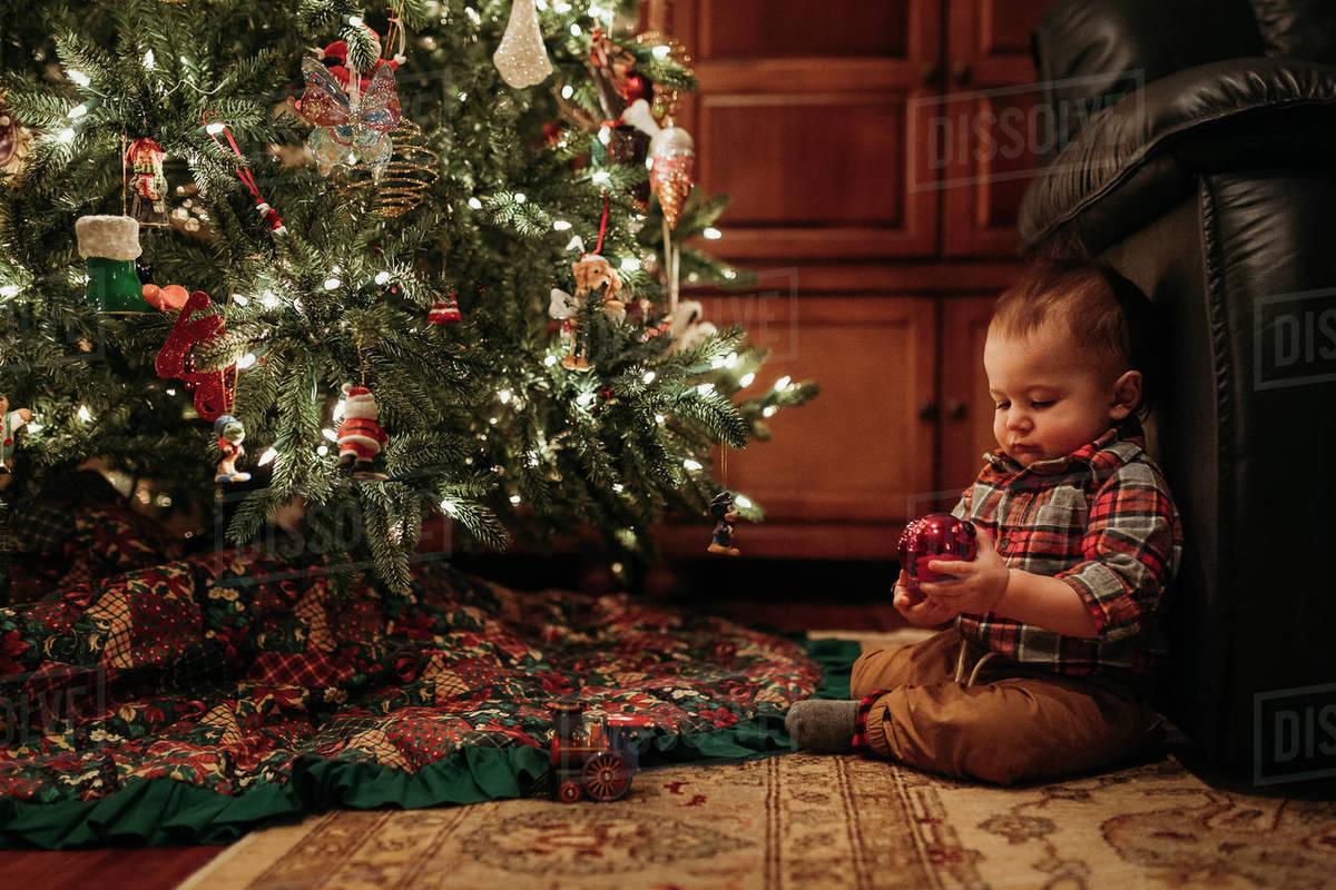 Toddler boy sitting under Christmas tree holding ornament Royalty-free stock photo