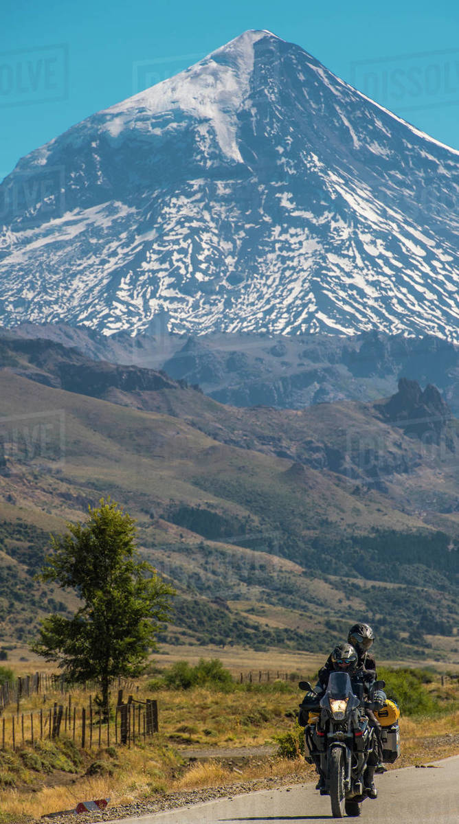 Couple on touring motorbike. Lanin volcano in the back, Argentina Royalty-free stock photo