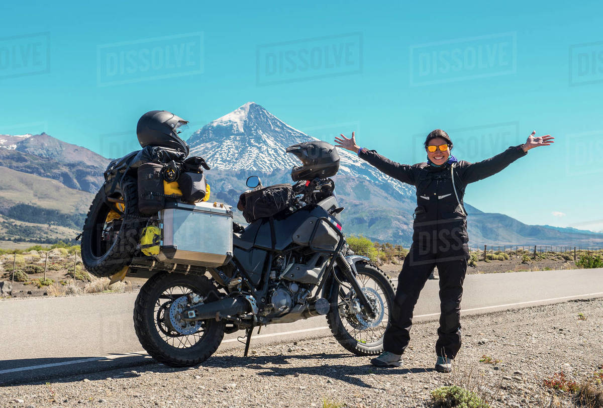 Woman standing next to touring motorbike. Lanin volcano in the back Royalty-free stock photo