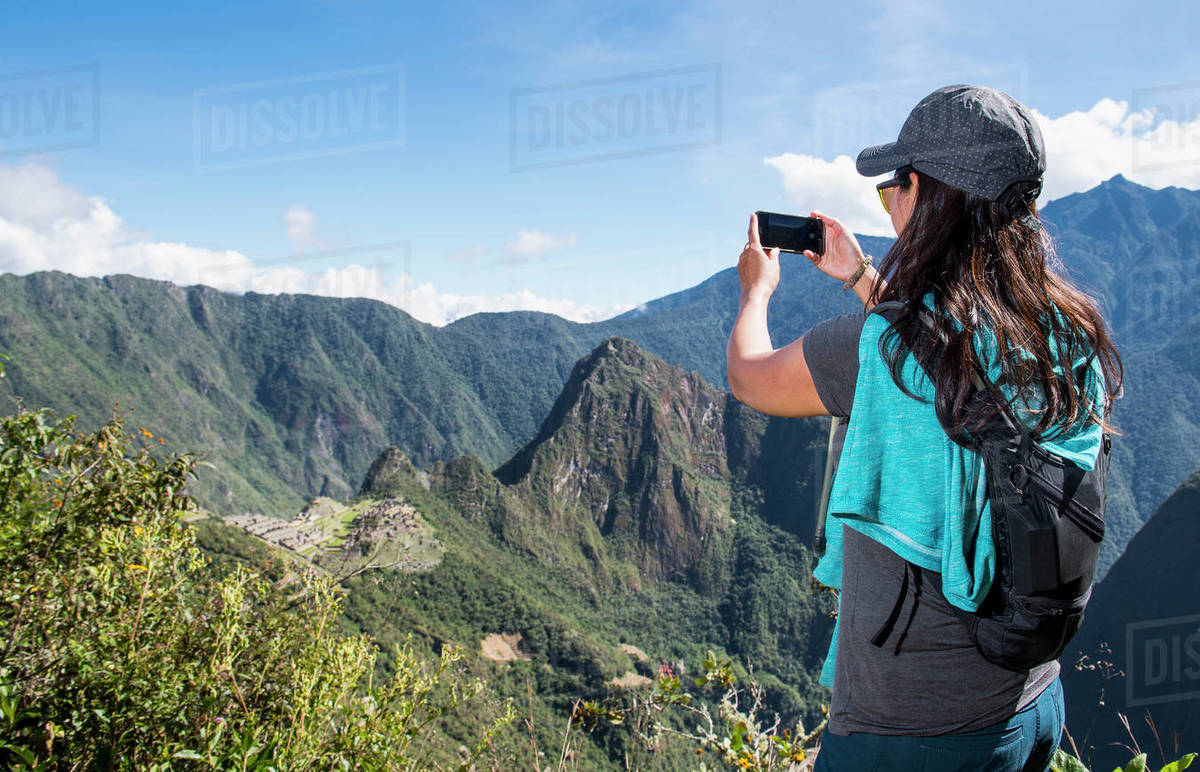 Woman takes a picture on smartphone of Machu Picchu on the Inca Trail Royalty-free stock photo