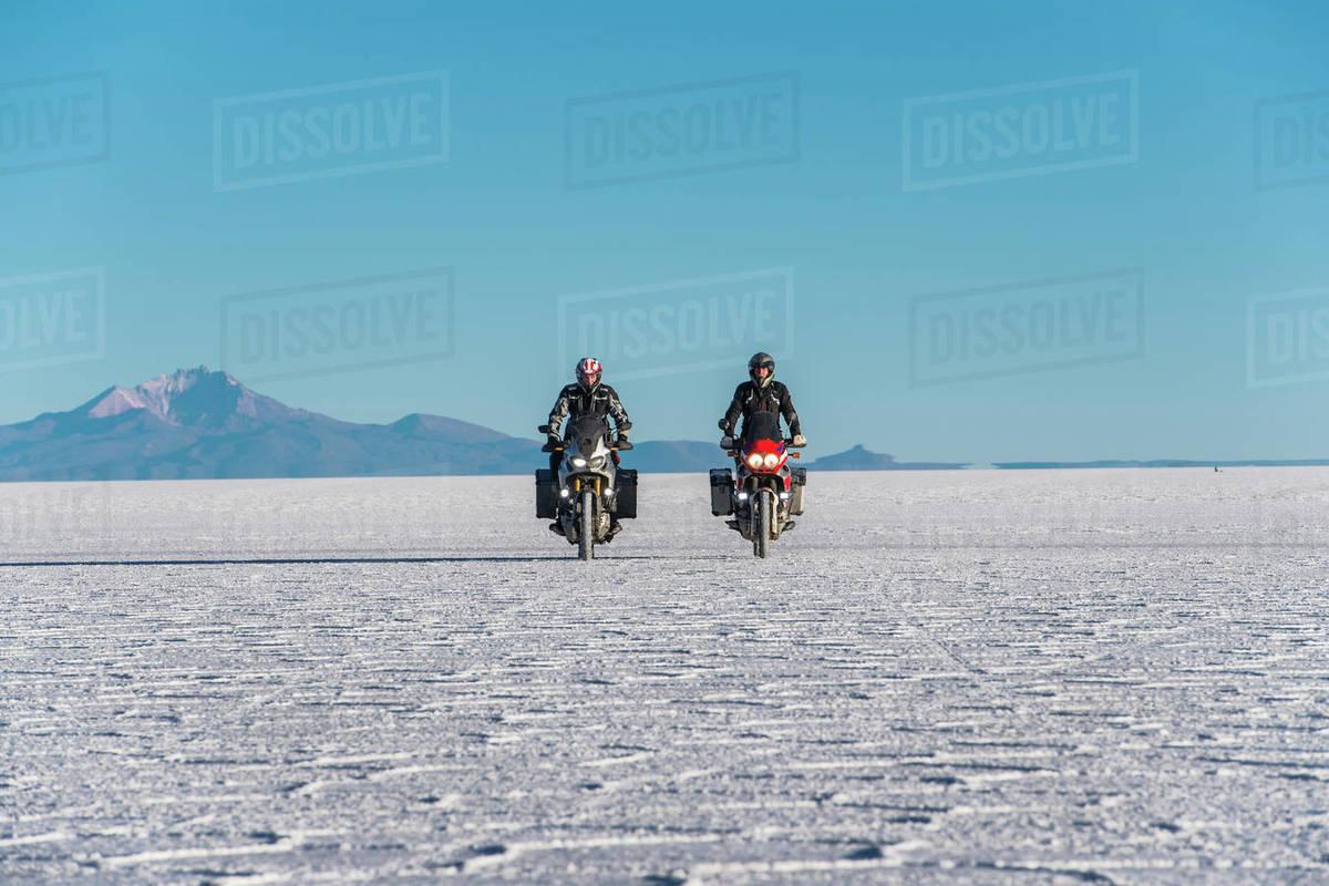 Two men riding touring motorbike's on the salt flats of Uyuni Royalty-free stock photo