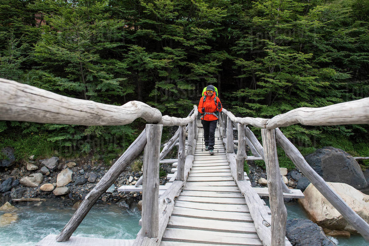 Female hiker crossing wooden bridge on the way up to Torres del Paine Royalty-free stock photo
