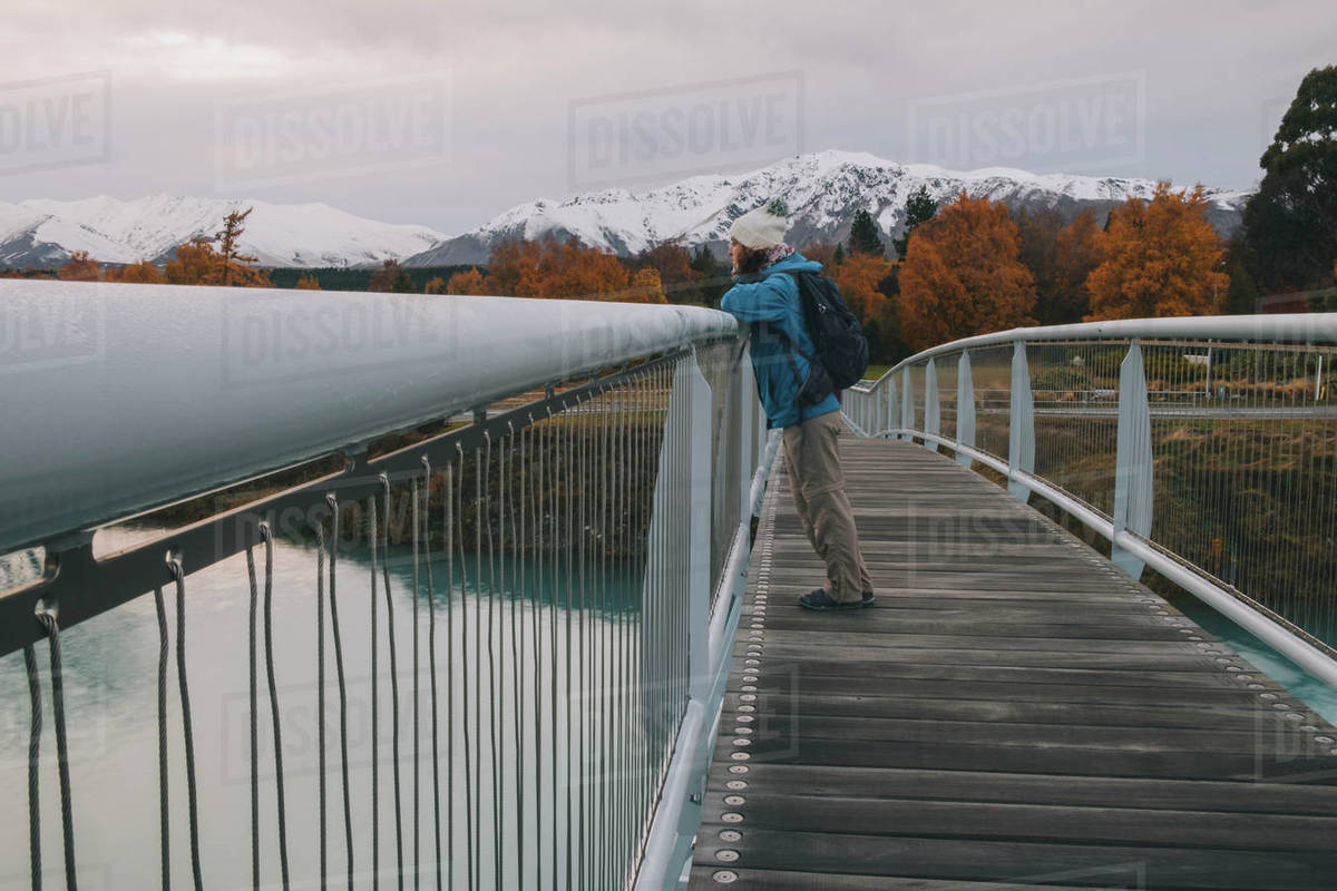 Woman looking at Lake Tekapo from bridge with mountains in background Royalty-free stock photo