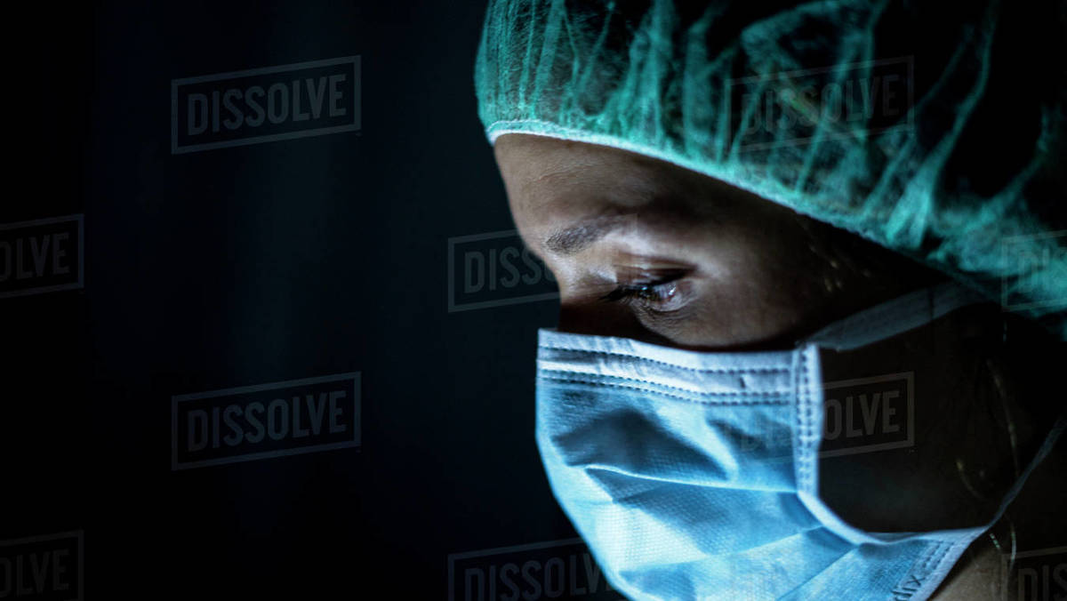 Portrait of young female surgeon, wearing mask and a surgical mask, in front of black background Royalty-free stock photo