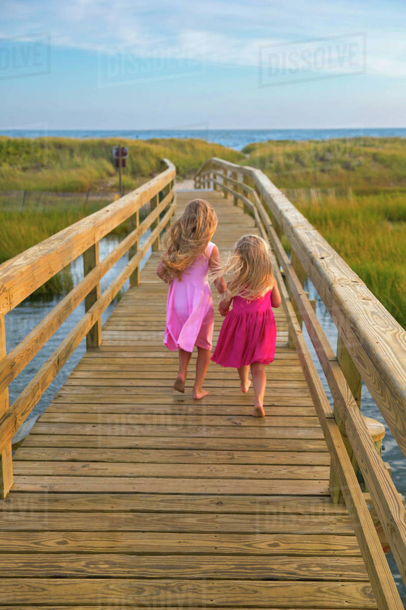 Little Girls From Behind Running On Bridge to Beach in Pink Dresses Royalty-free stock photo