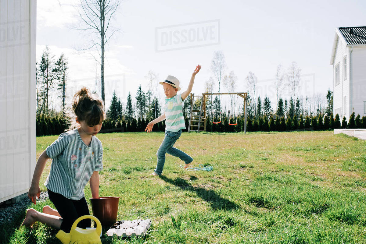 Boy dancing around the garden playing whilst his sister plants seeds Royalty-free stock photo