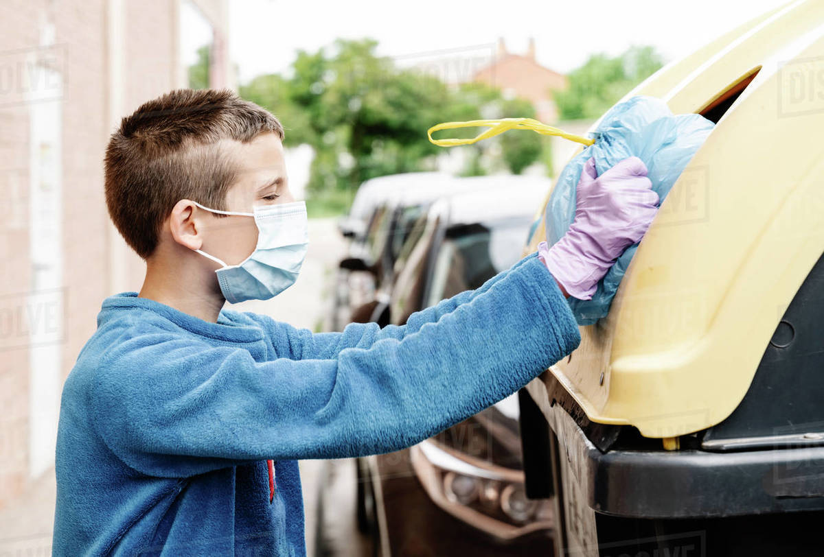 Boy throwing a blue trash bag into a yellow recycling container in the street. The kid wearing face mask and gloves is pushing the rubbish bag because it is too big to enter the bin. horizont Royalty-free stock photo