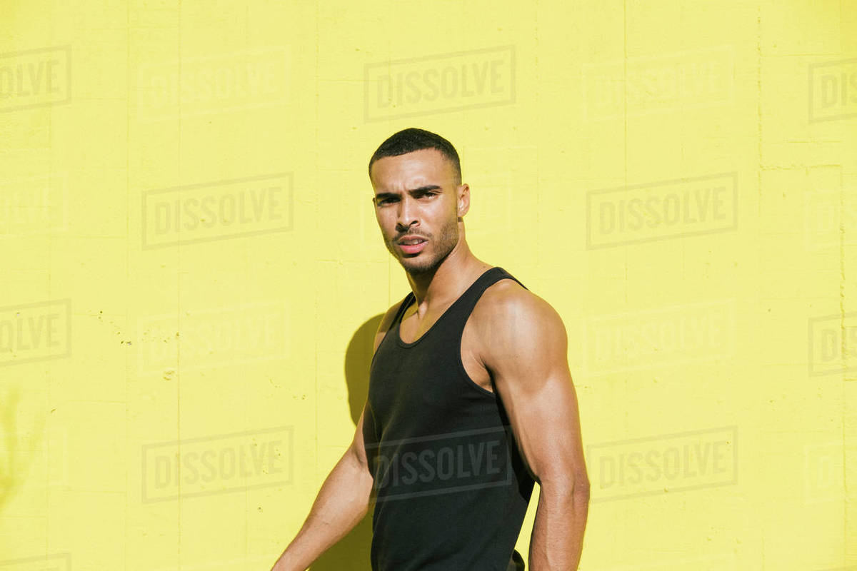 African American male athlete portrait against colorful yellow wall Royalty-free stock photo